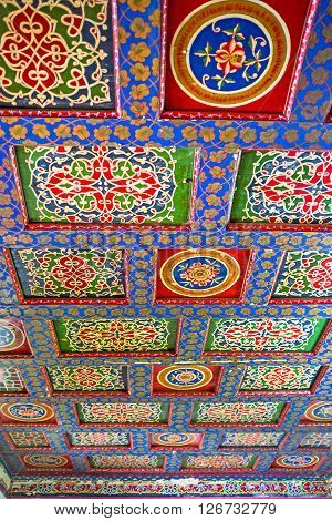 KOKAND UZBEKISTAN - MAY 6 2015: The carved wooden ceiling in Khudayar Khan Palace consists of many colorful screens and frames between them decorated with beautiful islamic patterns on May 6 in Kokand.