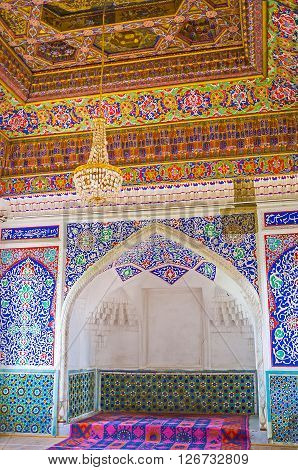 KOKAND UZBEKISTAN - MAY 6 2015: The Great Throne Room in Khudayar Khan Palace with the carved throne niche surrounded by islamic floral patterns and glazed tiles on May 6 in Kokand.