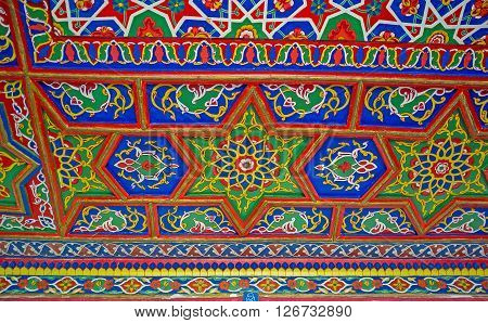 KOKAND UZBEKISTAN - MAY 6 2015: The colorful wooden ceiling in Khudayar Khan Palace decorated with the stellar and floral patterns in eastern style on May 6 in Kokand.