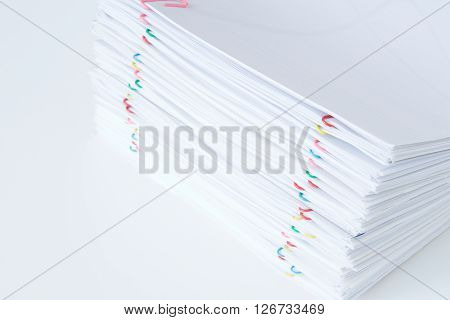 Colorful paper clip with pile of overload document and reports place on white table.