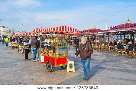ISTANBUL TURKEY - JANUARY 21 2015: The Eminonu promenade boasts many facilities to eat - there are many cozy cafes and carts with fresh bakery hot corn or roasted chestnuts on January 21 in Istanbul.