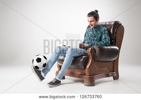 Portrait  of young man with laptop and football ball on gray background. concept of continuous soccer practice