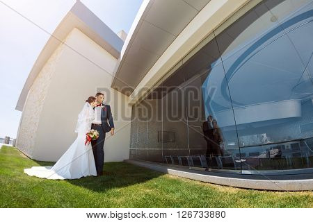 Young wedding couple enjoying romantic moments outside against modern buildings. Fisheye lens photo