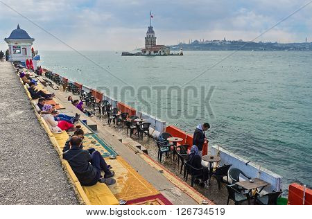 ISTANBUL TURKEY - JANUARY 21 2015: The outdoor teahouse on the Uskudar embankment with the carpets and sofas on the stairs with the view on the Maiden's Tower on January 21 in Istanbul.
