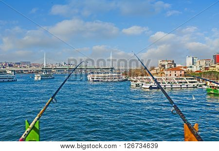 ISTANBUL TURKEY - JANUARY 21 2015: The view through the fishing rodson the beautiful Golden Horn Bay with numerous ferries and the Metro Bridge on the background on January 21 in Istanbul.