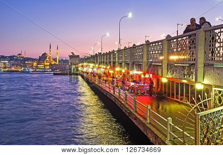 ISTANBUL TURKEY - JANUARY 21 2015: The bright lights on the ground level of Galata bridge attracts people to the fine fish restaurants and cozy cafes located there on January 21 in Istanbul.