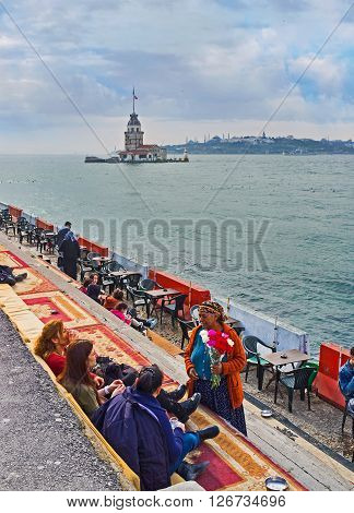 ISTANBUL TURKEY - JANUARY 21 2015: The elderly gypsy woman sells the flowers in the outdoor teahouse with the view on the Maiden's Tower on January 21 in Istanbul.