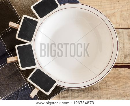 blank signboard with empty white plate on wooden table