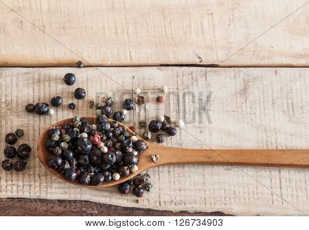 whole peppercorns on wooden spoons