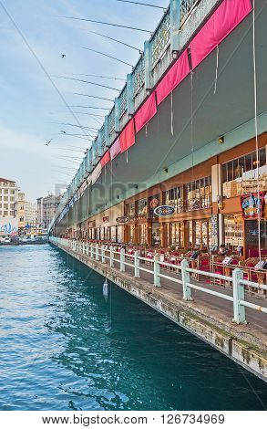 ISTANBUL TURKEY - JANUARY 21 2015: The cozy cafes and restaurants on Galata bridge with the numerous fishing rods hanging from the its top level on January 21 in Istanbul.