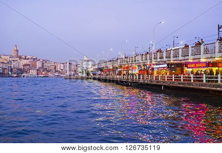 ISTANBUL TURKEY - JANUARY 21 2015: Two-level Galata bridge with the cafes and restaurants on the ground level and the numerous fishermen on the upper level on January 21 in Istanbul.