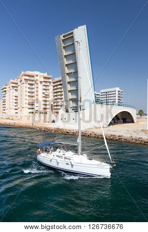 La Manga - SPAIN, AUGUST 25 2014: Drawbridge over water channel and Yacht at summer day