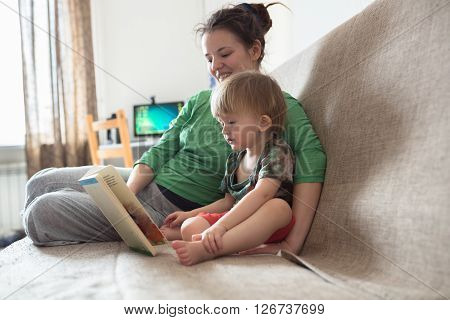 Young mother with her 2 years old little son dressed in home wear are relaxing weekend together read book lazy morning warm and cozy scene. Pastel colors selective focus.