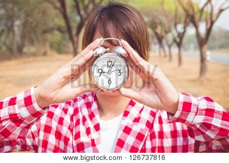 Young woman with alarm clock in a hand. vintage stype