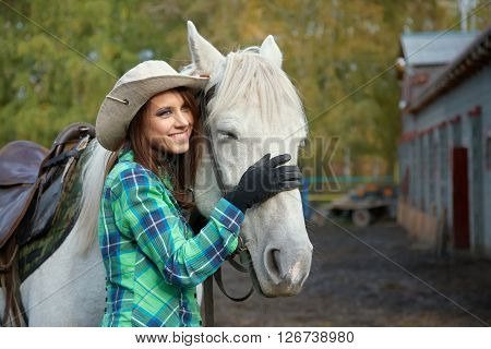 cute smiling cowgirl in a hat with a white horse