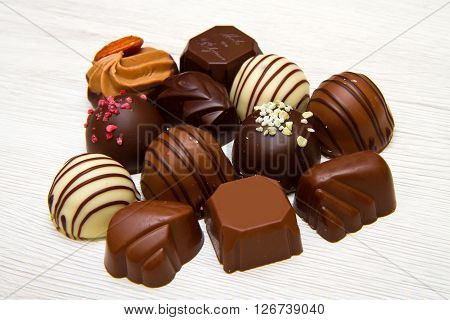 An assortment of fine chocolates in white dark and milk chocolate on white wood