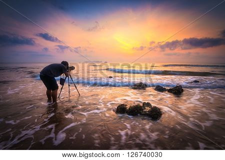 Silhouette of a photographer with dramatic waves at sunrise