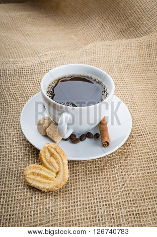 Cup of black coffee with foam cookie brown sugar coffee beans and cinnamon stick on sackcloth background