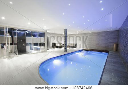 Relaxing indoor swimming pool with lighting and a corner for rest. Luxury resort swimming pool with beautiful clean blue water and light effects around the swimming pool.