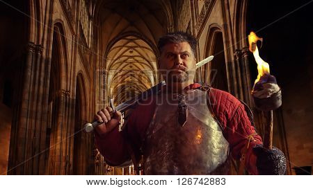 Medieval knight in the armor with the sword and flame on the ancient castle background.