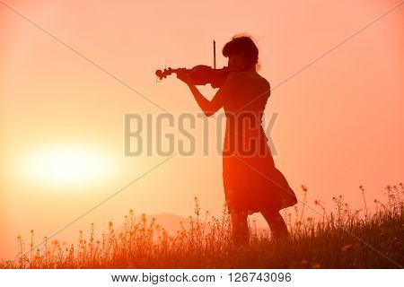 Woman Playing A Violin In A Red Sunset In Nature