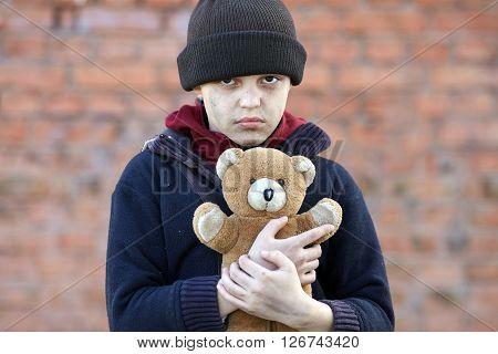 dramatic portrait of a little homeless boy holding a teddy bear