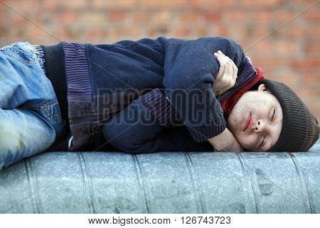 young homeless boy sleeping on a heating pipe city street