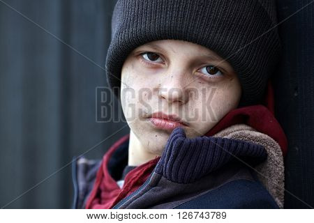 dramatic portrait of a little homeless boy poverty city street black wall
