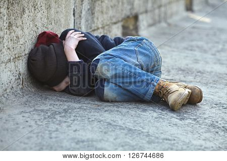 young homeless boy sleeping on the bridge poverty city street