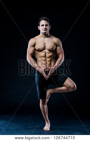 Muscular man balancing on the one leg feeling relaxed on dark background