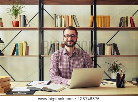 Smiling businessman with glasses looking at camera and typing on his laptop in his home office