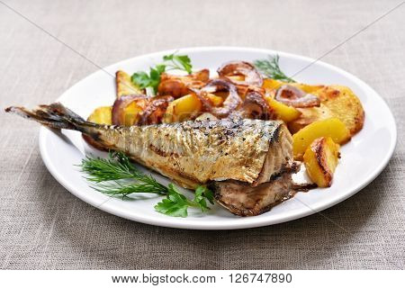 Fried mackerel fish with potato wedges on white plate