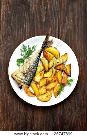 Baked potato wedges and mackerel fish on wooden background top view