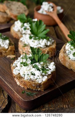Healthy food curd cheese and green herbs on wholegrain bread