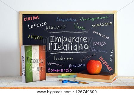 Blackboard in an Italian language classroom with the message Learn Italian (Imparare Italiano) and some other linguistic words.