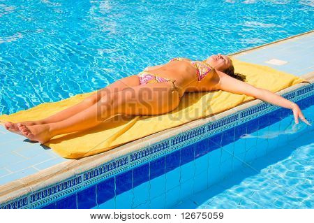 woman tanning under sun near pool