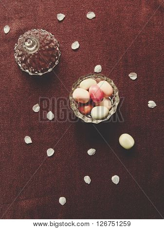 Glass bowl with candy and petals on a table. Top view