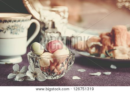 Candy in a glass bowl, surrounded by cups and plates. Warm retro tones