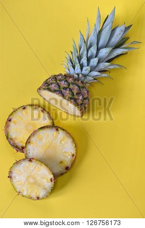 Pineapple slices isolated on yellow background, closeup
