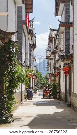 Lijiang, China - Oct 04, 2014: Chinese man drives on electric tricycle through a street amidst Chinese traditional architecture in Yunnan province, China