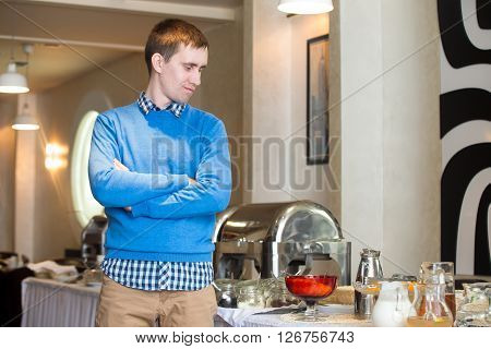 Portrait of young man at self-catering breakfast in hotel restaurant. Picky eater fed-up with food. Showing disappointment on his face
