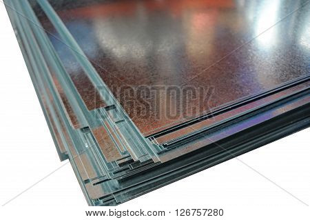Folded stack of shiny metallic sheets closeup at white background