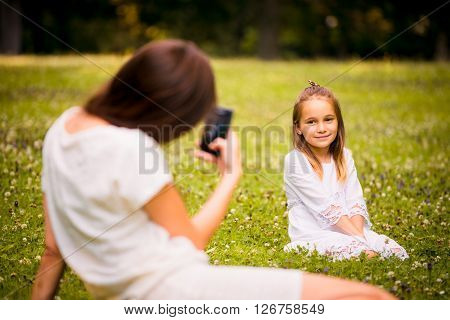 Mother taking photo of her child with phone camera outdoor in nature