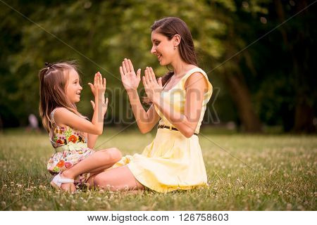 Clapping hands - mother playing with her daughter outdoor in nature