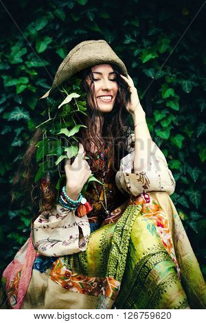 smiling young woman in silky boho style dress and ivy in hair and hat sit in garden summer day
