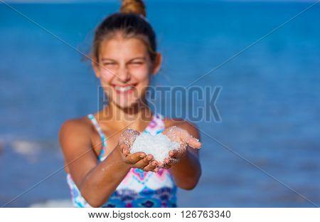 Portrait of beautiful girl holding sea salt for spa from Dead Sea. Israel. Focus on the salt