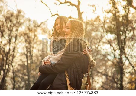 ZAGREB, CROATIA - 15 NOVEMBER 2015: Cheerfull mother holdes daughter in park on an autumn day.