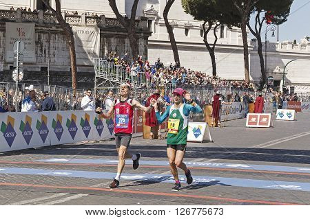 Rome, Italy - April 10, 2016: Two runners together at the finish line of the Fori Imperiali Avenue, during the Rome Marathon.