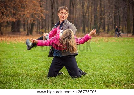 ZAGREB, CROATIA - 15 NOVEMBER 2015: Father and daughter play in park on an autumn day.