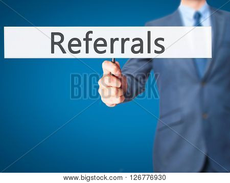 Referrals - Businessman Hand Holding Sign